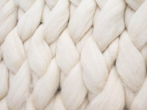 Eine Nahaufnahme von weißer, verarbeiteter Schafwolle.